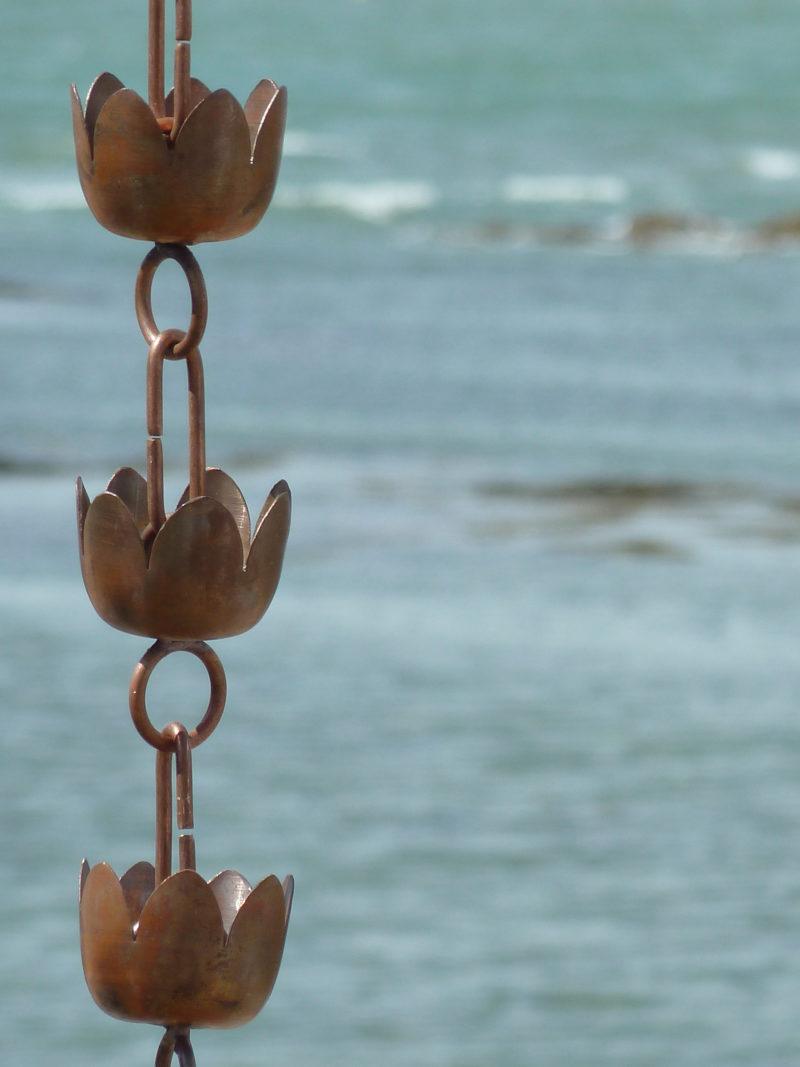 Ôtemachi est une Chaine de pluie composée de coupelles en forme de fleur de lys en cuivre patiné